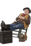 Smiling old cowboy sits in rocking chair with feet up