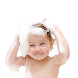 baby girl with soap suds on hair taking bath.