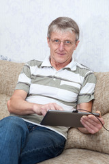 Senior adult Caucasian man working with a touchpad