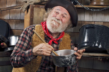 Old cowboy stirs saucepan in outdoor kitchen