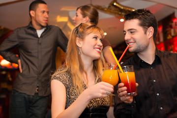 Junges Paar trinkt Cocktails in einer Bar oder Restaurant