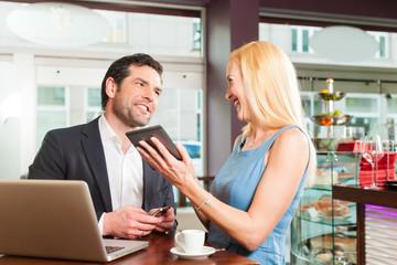 Arbeitskollegen - ein Mann und eine Frau - sitzen in einem Cafe