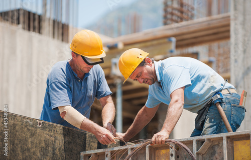 Construction workers working on cement formwork frames - 45348884