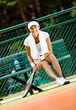 Young female tennis player rests with bottle of water
