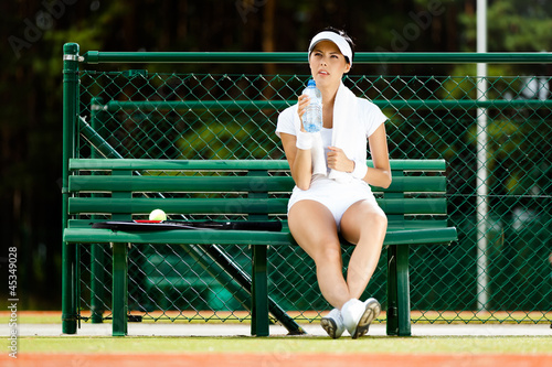 Female tennis player rests with bottle of water