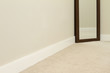 Empty room with carpet and mirror.