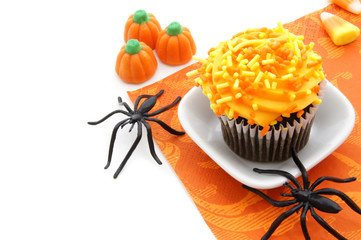 Halloween cupcake and candy with spiders over white