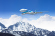 White passenger plane above the mountains
