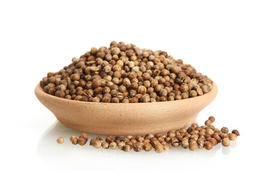 Heap coriander seeds in clay bowl isolated on white
