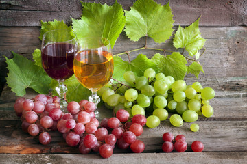 Glass of wine and grapes on old wooden boards