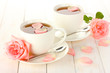 cups of tea with roses on white wooden table