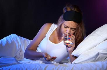 young beautiful woman with pills lying on bed in bedroom