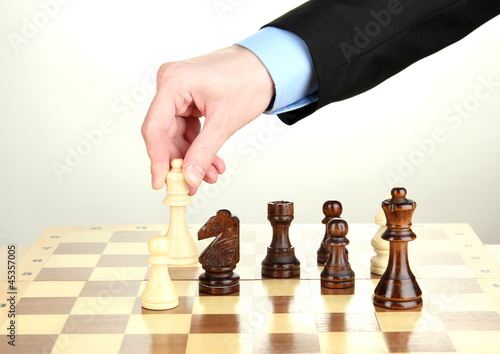 businessman playing chess isolated on white.