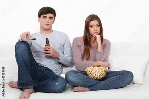 Bored man and woman watching TV