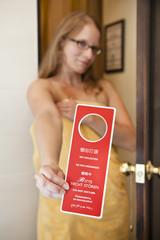 Frau mit Handtuch hält Bitte nicht stören Schild im Hotel