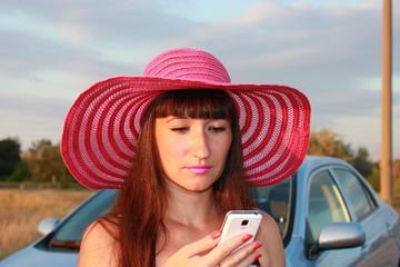 Девушка возле автомобиля смотрит в телефон