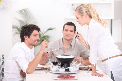 Three people enjoying fondue