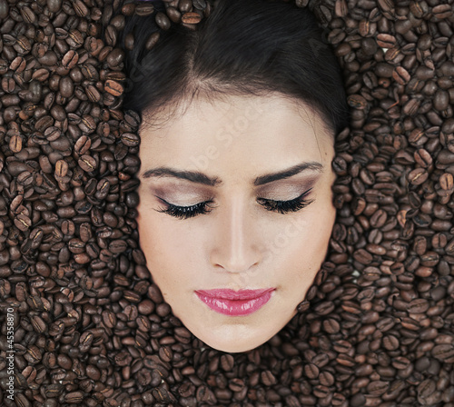 Beautiful face of brunette among coffe beans