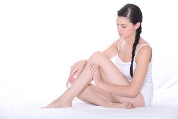 Woman in white underwear shaving her legs