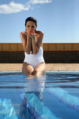 Brunette sat poolside blowing kiss