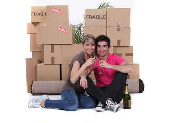 Couple surrounded by belongings and drinking champagne