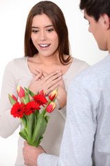 Woman being surprised with bunch of flowers