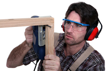 Carpenter sawing into wooden frame