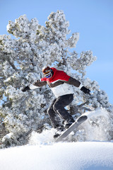 Man performing jump on snowboard