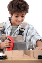 Closeup of a young boy sawing word