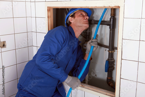 Plumber feeding blue pipe behind a wall