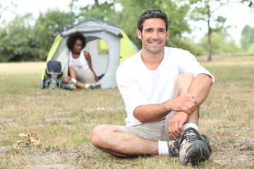 Mixed race couple camping in tent