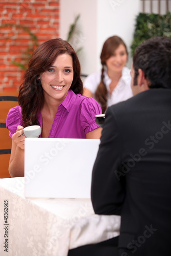 Couple drinking expresso and looking a computer
