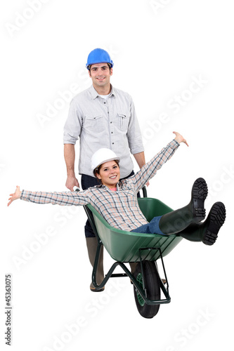 Builder couple using wheelbarrow