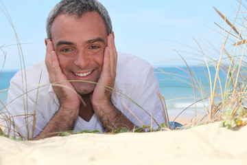 Happy man lying on the sand