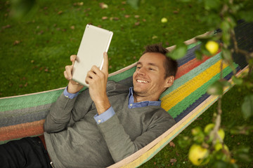 young man reading tablet in hammock