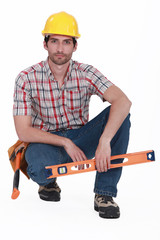 Handyman kneeling with spirit-level