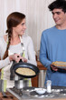 A young couple making crepes.