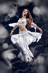 Beautiful active belly dancer woman in white dress over black