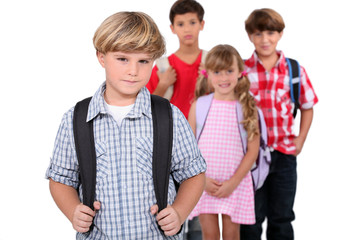 Four schoolchildren with backpacks