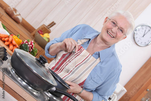 Old lady cooking in kitchen