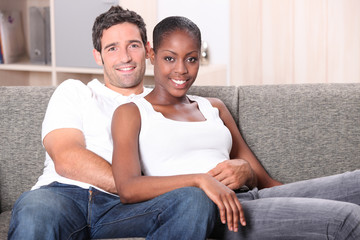 Mixed race couple sat on sofa