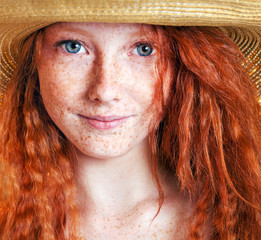 Beautiful freckled young woman wearing straw hat