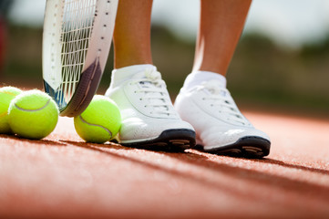 Legs of athlete near the tennis racket and balls
