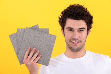 Man holding up tiles