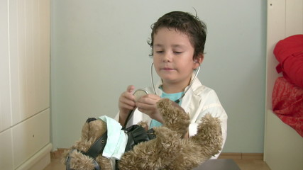 Little boy with a bear playing a doctor