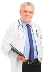 A mature doctor holding a clipboard and posing