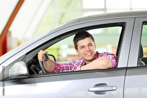 Smiling male sitting in his automobile and holding a key