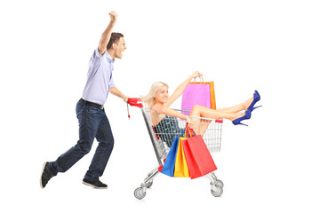 Excited person pushing a shopping cart, happy woman with bags in