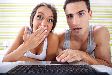 Surprised couple front of laptop