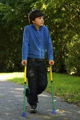 Gehbehinderter Junge mit Gehhilfen